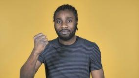 Uomo africano casuale arrabbiato combattente isolato su fondo giallo stock footage