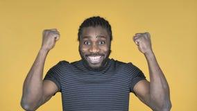 Uomo africano casuale che celebra successo isolato su fondo giallo video d archivio
