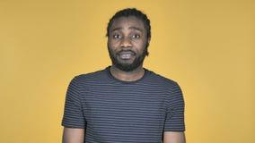 Uomo africano casuale che scuote testa per rifiutare isolato su fondo giallo video d archivio