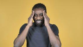 Uomo africano casuale con l'emicrania isolato su fondo giallo video d archivio