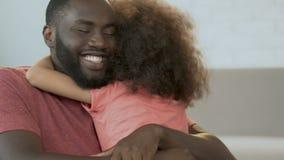 Uomo africano che abbraccia sua figlia sveglia e che sorride, paternità, comodità della famiglia video d archivio