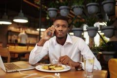 Uomo africano che parla al telefono di chiamata cenando al caffè Fotografia Stock