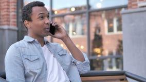 Uomo africano che parla sulla seduta del telefono all'aperto stock footage