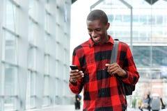 Uomo africano che per mezzo del telefono cellulare alla stazione ferroviaria Immagine Stock Libera da Diritti