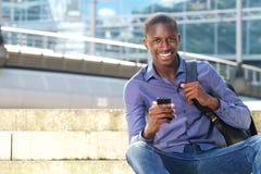 Uomo africano che si siede all'aperto con il telefono cellulare e sorridere Immagini Stock