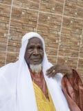 Uomo africano che si siede davanti alla sua casa, ottanta anni fotografia stock