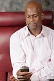 Uomo africano che texting Immagini Stock Libere da Diritti