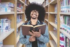Uomo africano che tiene un libro nella biblioteca Immagini Stock
