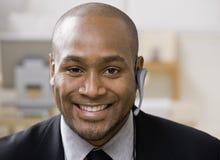 Uomo africano con l'unità hands-free del telefono delle cellule Immagini Stock