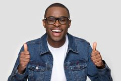 Uomo africano felice che mostra i pollici sulla macchina fotografica di sguardo di risata fotografie stock