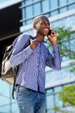 Uomo africano felice che parla sul telefono cellulare e sul sorridere Fotografia Stock Libera da Diritti