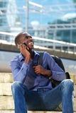 Uomo africano felice che parla sul telefono cellulare e sul sorridere Immagine Stock Libera da Diritti