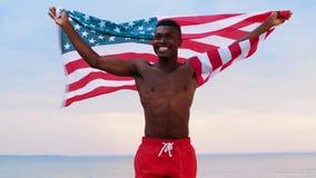 Uomo africano felice con la bandiera americana sulla spiaggia video d archivio
