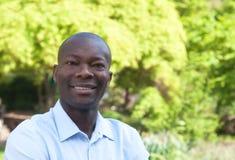 Uomo africano felice in parco che esamina macchina fotografica Fotografia Stock Libera da Diritti