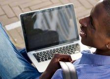 Uomo africano giovane felice con il computer portatile Fotografia Stock Libera da Diritti