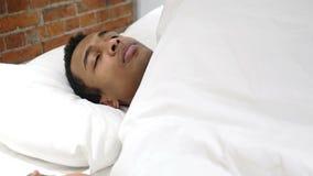 Uomo africano scomodo che dorme a letto alla notte, irrequietezza video d archivio