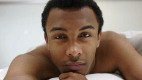 Uomo africano serio che si trova sullo stomaco, guardante in camera stock footage