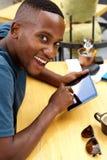 Uomo africano sorridente al caffè con un computer della compressa Immagini Stock Libere da Diritti
