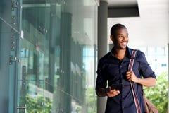 Uomo africano sorridente che cammina con il telefono cellulare e la borsa Immagini Stock Libere da Diritti
