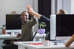 Uomo africano sorridente che dà gli alti cinque ad un collega maschio immagini stock libere da diritti