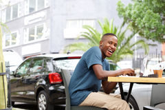 Uomo africano sorridente che si siede ad una caffetteria all'aperto Immagini Stock