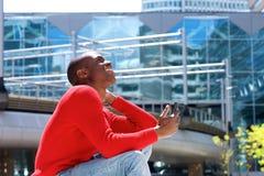 Uomo africano sorridente che si siede fuori con il cellulare a disposizione Fotografia Stock Libera da Diritti