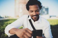 Uomo africano sorridente dei giovani che invia messaggio di testo dallo smartphone mentre sedendosi al parco soleggiato della cit Fotografie Stock Libere da Diritti