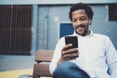 Uomo africano sorridente dei giovani che per mezzo dello smartphone per ascoltare musica mentre sedendosi sul banco alla via sole Immagini Stock