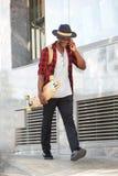 Uomo africano sorridente dell'ente completo con il pattino che parla sul telefono cellulare Fotografia Stock