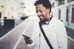 Uomo africano sorridente felice che per mezzo dello smartphone all'aperto Ritratto di giovane uomo allegro nero che manda un sms  Fotografia Stock Libera da Diritti