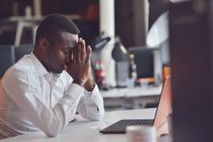Uomo africano stanco che si siede ad un ufficio dopo un giorno feriale duro, lavorando al computer portatile, provante a concentr immagini stock libere da diritti