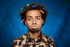 Uomo africano triste con gli indicatori in capelli sopra fondo blu fotografie stock