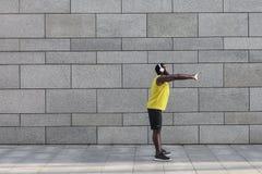 Uomo afroamericano in abiti sportivi gialli che allungano prima dell'allenamento Fotografia Stock