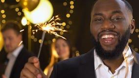 Uomo afroamericano allegro che tiene la luce di Bengala al partito che celebra nuovo anno stock footage