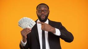 Uomo afroamericano allegro in formalwear che indica al mazzo di contanti del dollaro, vettura archivi video
