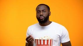 Uomo afroamericano annoiato con popcorn che guarda programma privo d'interesse della TV, primo piano fotografia stock