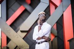 Uomo afroamericano attraente bello in occhiali da sole che posano accanto ciao alla costruzione moderna di tecnologia su una via immagini stock libere da diritti