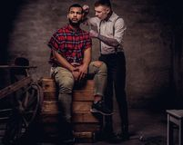 Uomo afroamericano bello che ottiene un taglio di capelli mentre sedendosi sulle scatole di legno ad uno studio Professionista an fotografia stock libera da diritti