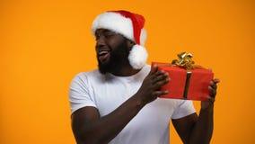 Uomo afroamericano in cappello di Santa che tiene il regalo di Natale e che sbatte le palpebre, festa stock footage