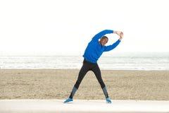 Uomo afroamericano che allunga i muscoli alla spiaggia Immagine Stock
