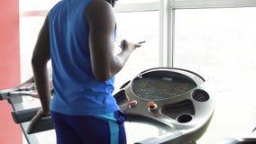 Uomo afroamericano che cammina sulla pedana mobile e che controlla il suo smartphone nella palestra archivi video