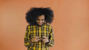 Uomo afroamericano che gioca gioco su Smartphone su fondo arancio Concetto delle emozioni archivi video
