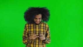 Uomo afroamericano che gioca gioco su Smartphone sullo schermo verde o sul fondo chiave di intensità Concetto delle emozioni archivi video