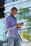 Uomo afroamericano che gode della musica sul suo telefono cellulare Fotografie Stock