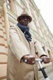 Uomo afroamericano che guida motorino elettrico fotografia stock libera da diritti