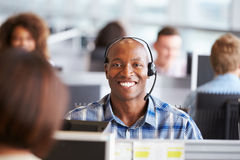 Uomo afroamericano che lavora nel call-center, sguardi alla macchina fotografica immagine stock libera da diritti