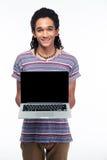 Uomo afroamericano che mostra lo schermo in bianco del computer portatile Immagine Stock