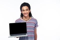 Uomo afroamericano che mostra lo schermo in bianco del computer portatile Fotografia Stock Libera da Diritti
