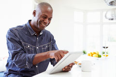 Uomo afroamericano che per mezzo della compressa di Digital a casa Fotografie Stock Libere da Diritti