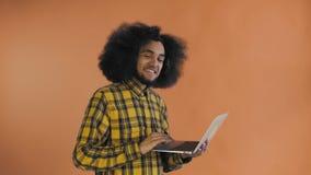 Uomo afroamericano che scrive al computer portatile e che sorride sul fondo arancio Concetto delle emozioni archivi video